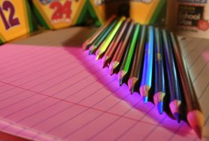 photo of colored pencils and crayon boxes on top of lined paper